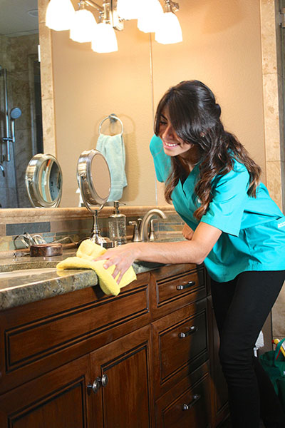 Naked Clean maid cleaning bathroom counter top with green cleaning products. San Diego, CA house cleaning service