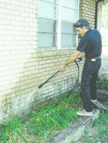 Worker powerwashing brick house before tuckpointing.