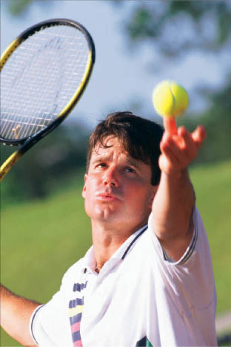 man tossing tennis ball to serve during a tennis game