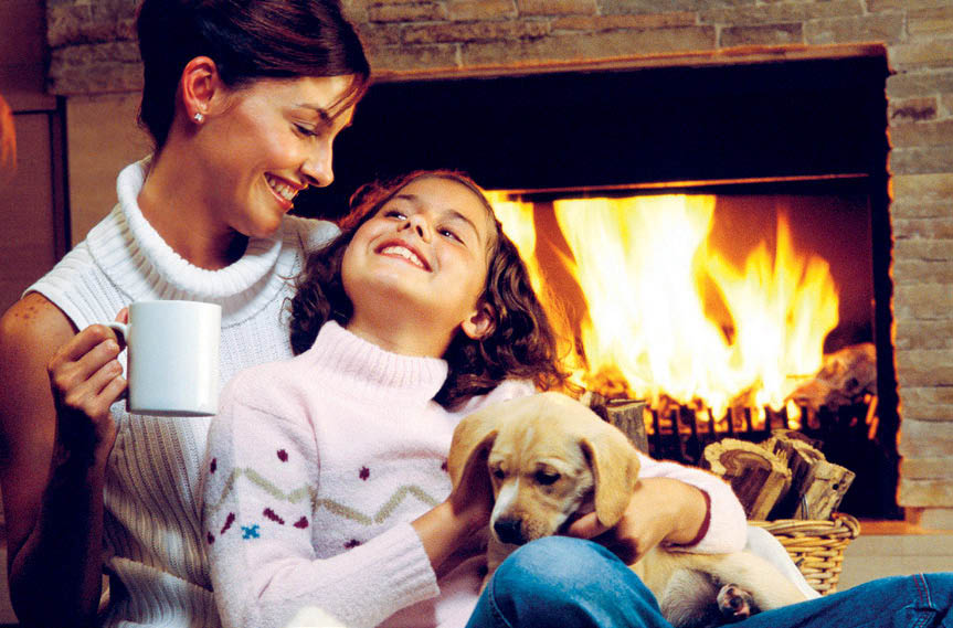 Mother and daughter sitting by a fireplace smiling in Racine