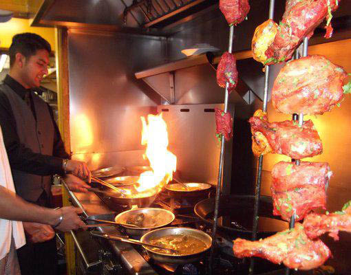 Cooks preparing Indian food at India's Tandoori in California