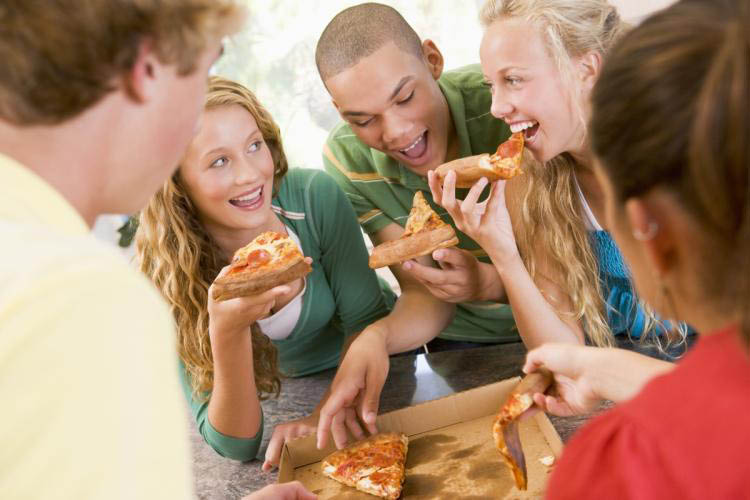 group of people eating pizza together