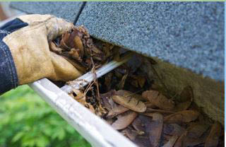 photo of hand clearing leaves from gutter system by All Phases Home Service in Ann Arbor, MI