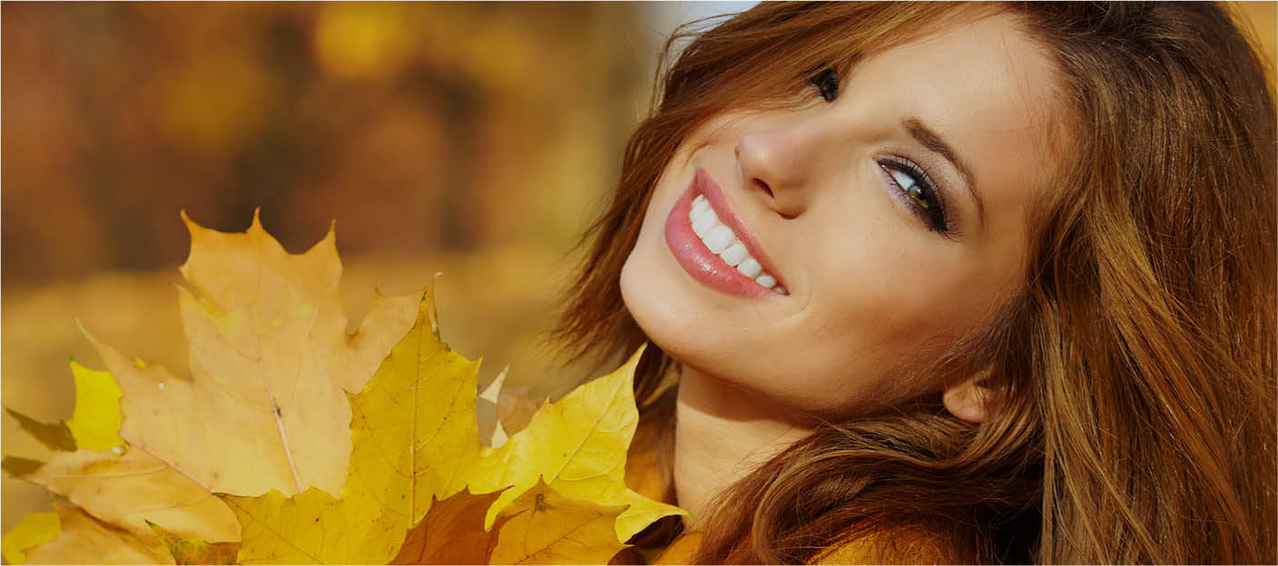 Girl smiling with autumn leaves nearby