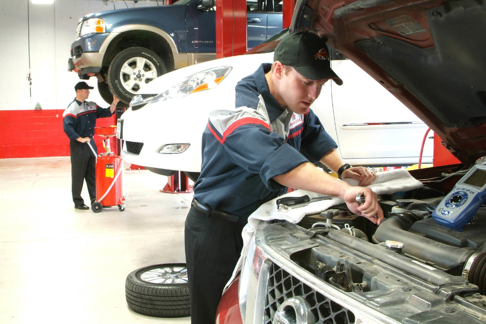 ASE certified technician from Brakes Plus working on a car