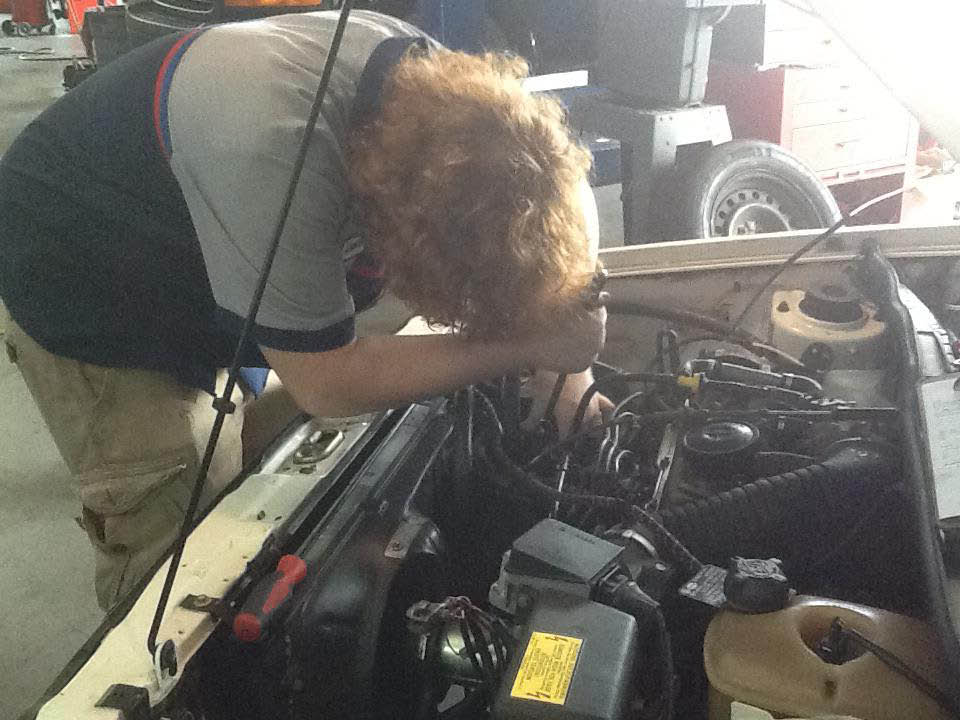 auto mechanic working on car engine at Auto Tech Car Care in Deefield Beach, FL