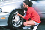 photo of woman shining her new tires from Belanger Tire & Auto Service in Westland, MI
