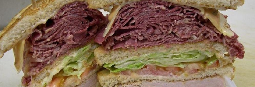 photo of stacked deli sandwitch from The Bread Basket Deli or Al's Famous Deli