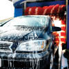 Black car with soapy suds emerging from car wash