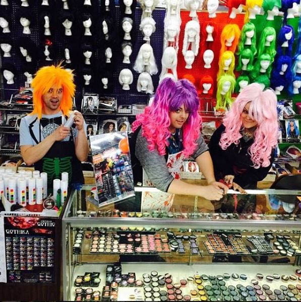 Employees of Champion Party Supply wearing wigs at the counter - Seattle, WA