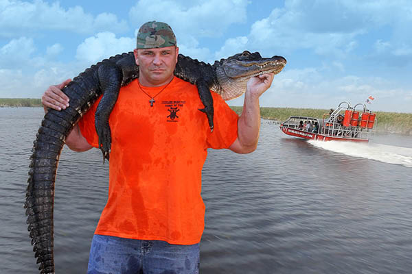 Man poses with alligator at Everglades Holiday Park