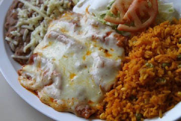 Enchiladas plate with Spanish rice and refried beans, lettuce and tomato..
