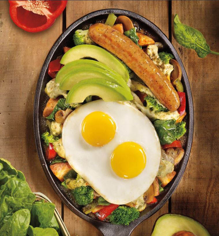 A breakfast skillet with sunny side up eggs and avocado