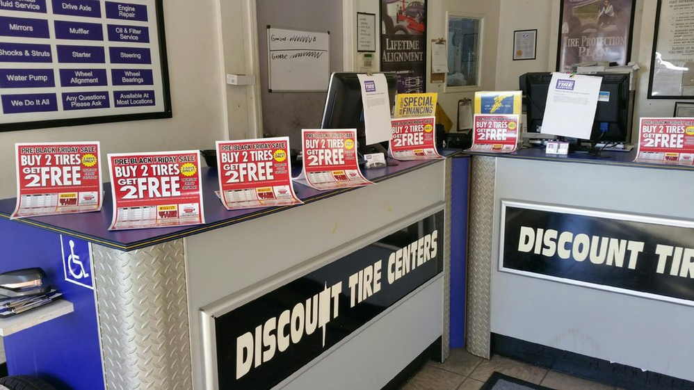 inside automotive sales counter with auto service and tire specials at Discount Tire Centers