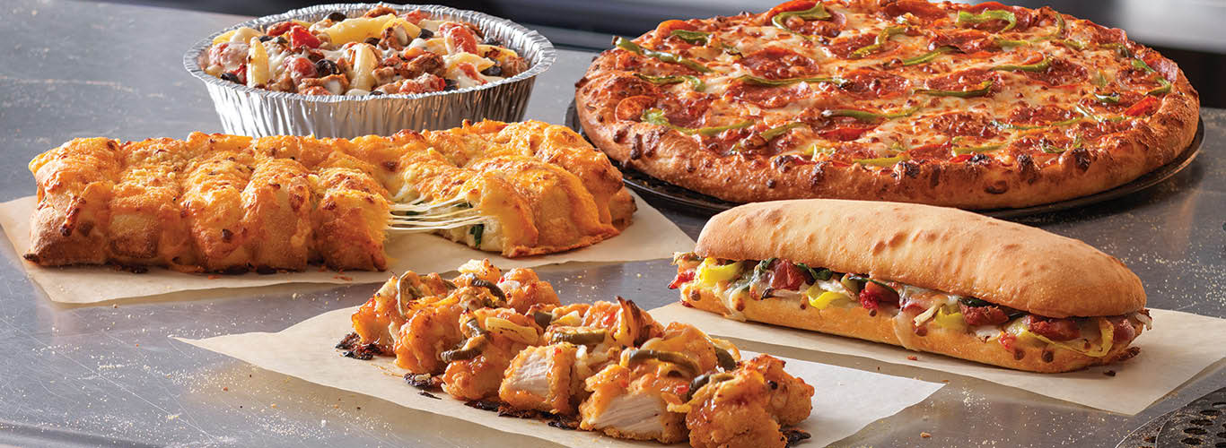 Image of Pizza, Oven-Baked Sandwiche, Pasta dish, Stuffed Cheesy Bread, and Chicken Wings displayed on counter