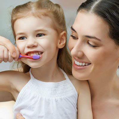 young girl brushing her teeth beside her mother