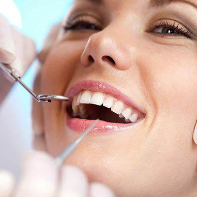 dental hygienist performing an oral exam