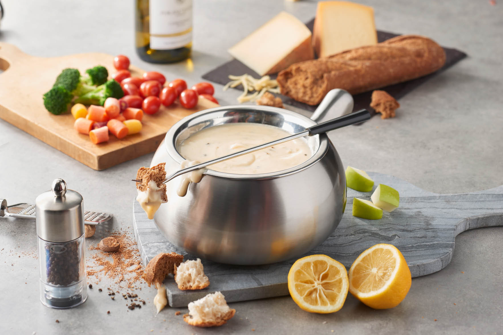 Cheese fondue with vegetables, bread and fresh fruit