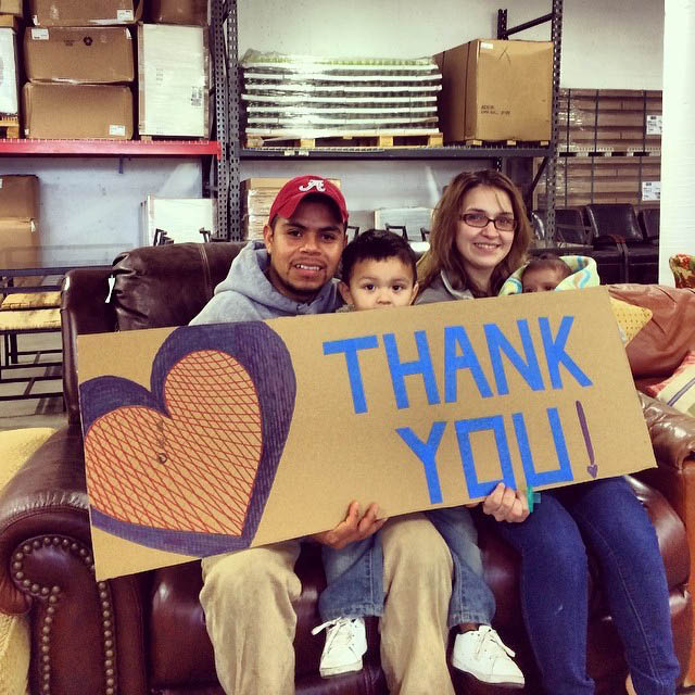 NW Furniture Bank helps restore hope and dignity to struggling families - family holding a thank you sign at NW Furniture Bank in Tacoma, WA