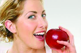 woman ready to bite into apple with clean white teeth