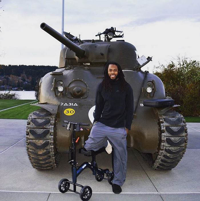 Seattle Seahawks' Richard Sherman standing in front of a Sherman Tank at the Flying Heritage & Combat Armor Museum in Everett, WA
