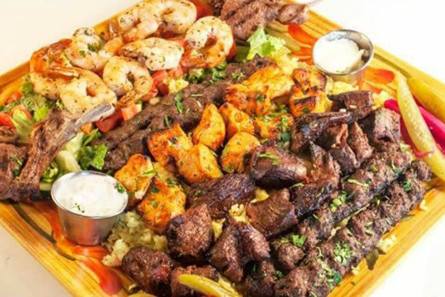 Wide selection of meat kabobs including shrimp, steak and chicken on a bed of greens.