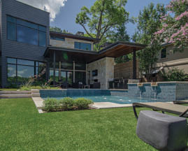 Two story grey house with waterfall and pool