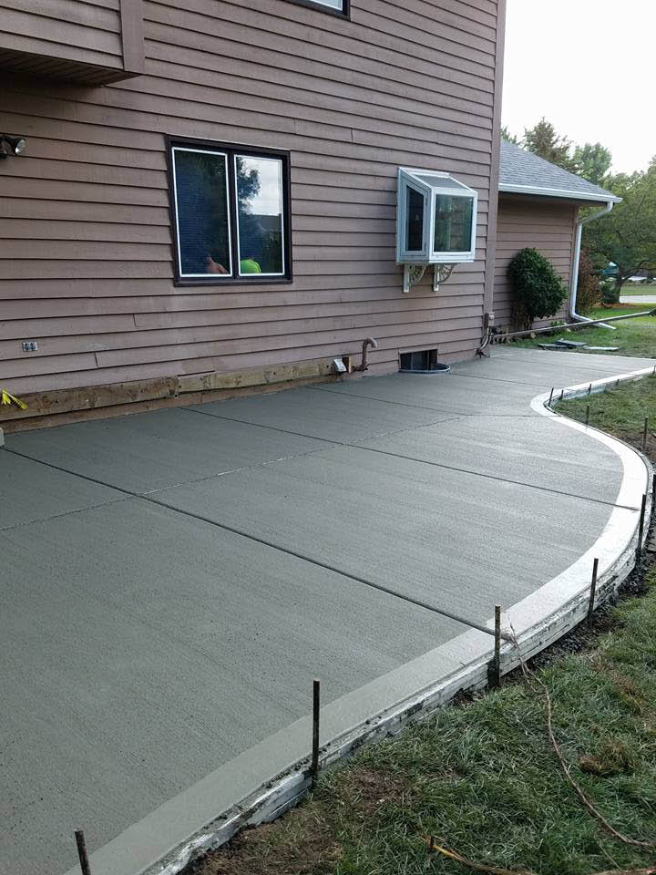 newly poured curved concrete patio abutting a brick house in Wisconsin; concrete companies.
