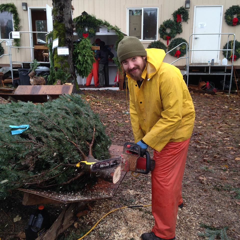 Friendly employee at Donna's Trees freshly cutting a Christmas tree so it can drink in the most water possible