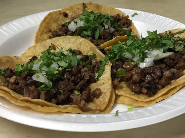 Plate of steak tacos with oniion and cilantro.