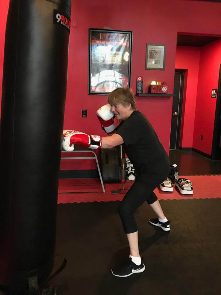 Woman punching a bag at 9Round 30 Min Kickbox Fitness - Gig Harbor, WA - Gig Harbor fitness clubs - kickboxing - total body workout - fitness coupons near me