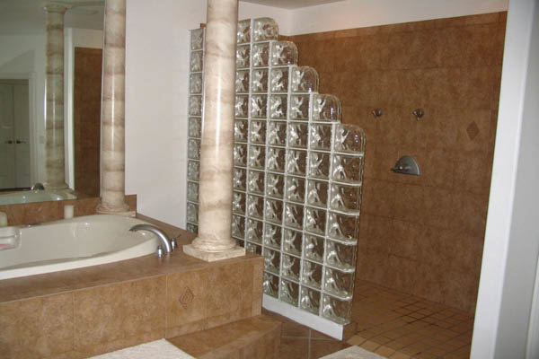 A wall of decorative glass blocks in a bath and shower