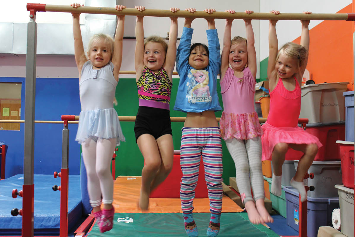 Preschoolers hanging by a parallel bar in gym class.