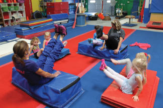 4/5 year olds performing gross motor skill exercises on mats.