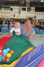Mom and infant playing with parachute and plsstics balls in class at Gym-Kinetics in Mokena, Il.