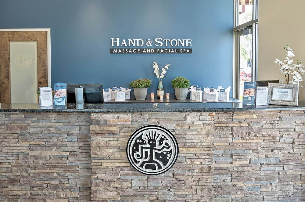 Hand & Stone Massage Spa Greeting Area Soothing Hot Stone Massage Therapists Hands on Back
