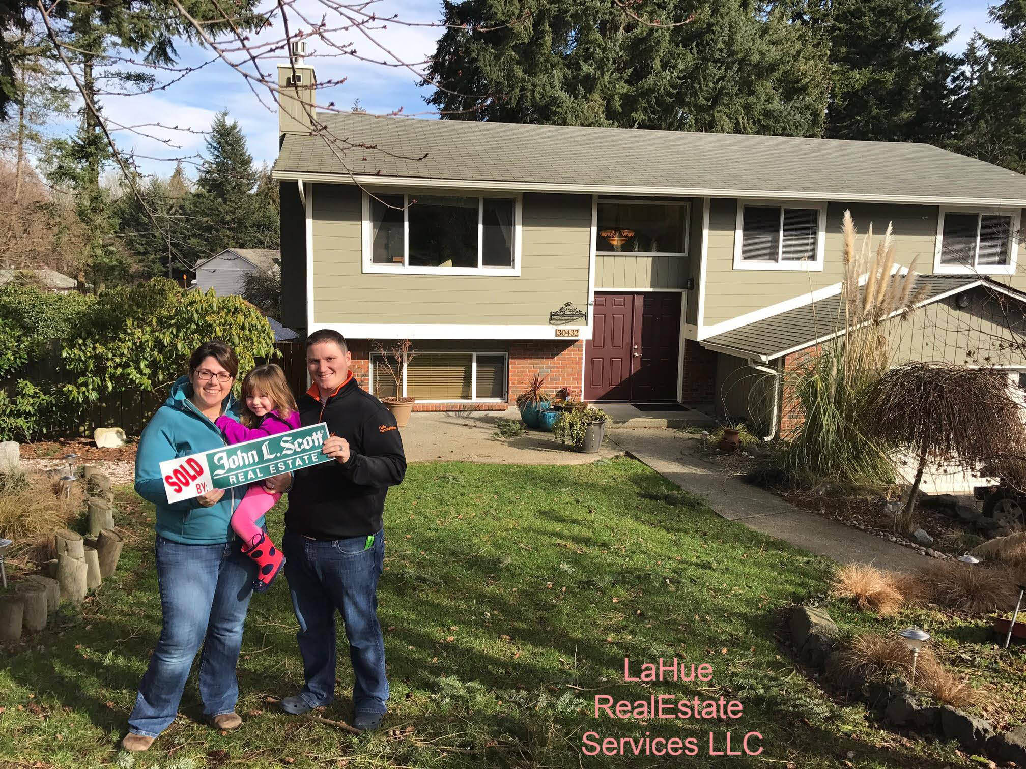 Happy family standing in front of their new home that they bought through John L. Scott Real Estate Company of Des Moines, WA