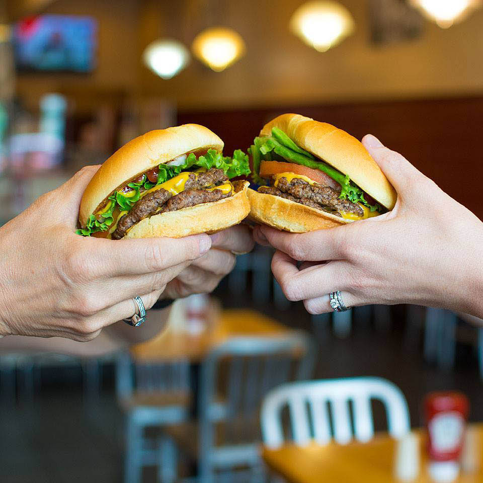 Inside Wayback Burgers restaurant in Bellevue, Washington - two people holding up hamburgers from Wayback Burgers