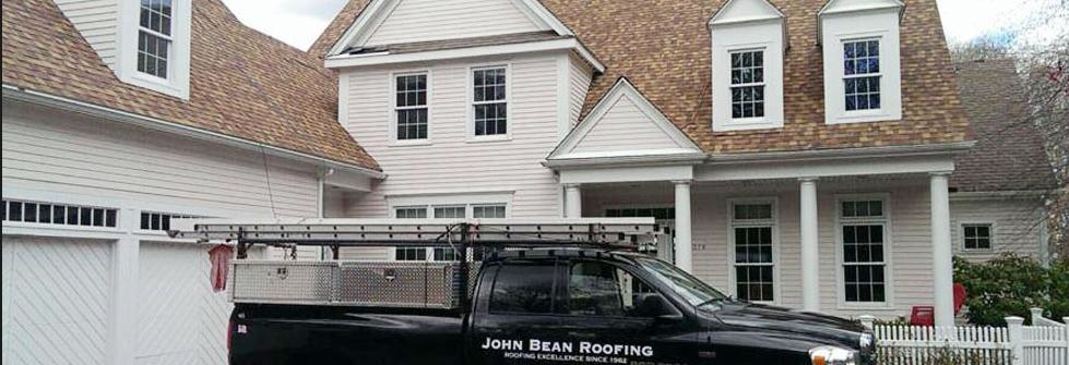 JB Roofing vehicle in front of newly roofed house