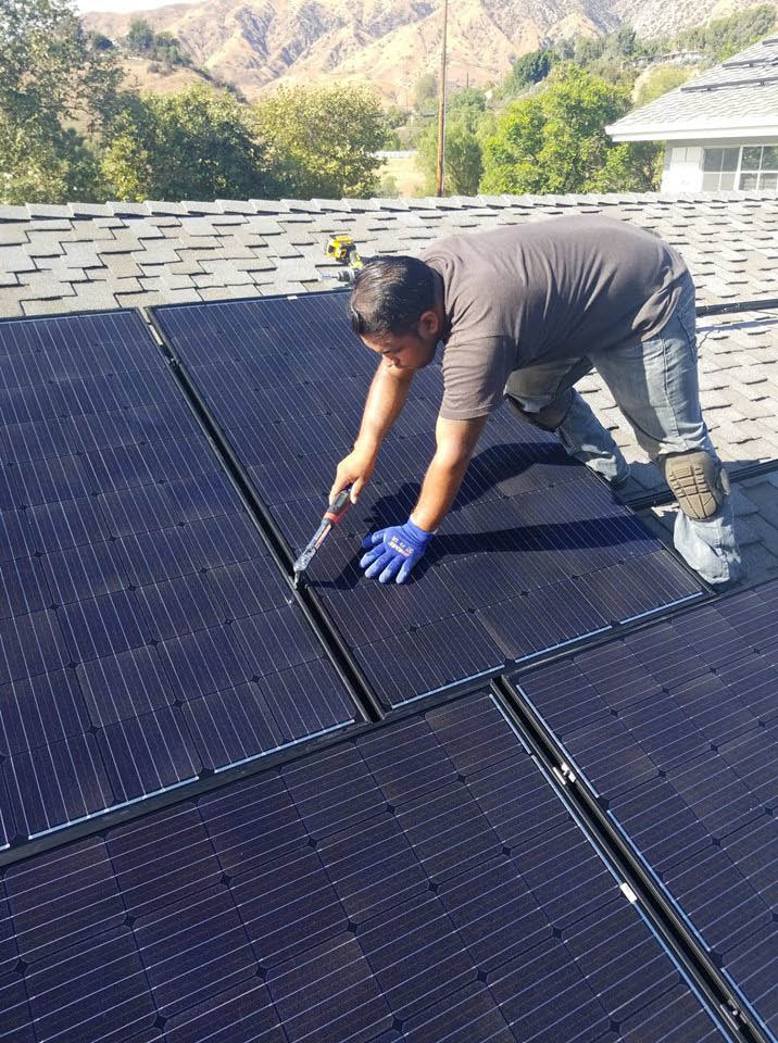 Solar panels being installed on a roof by a technician from Jeremy's Electric in Tujunga, CA - solar power for heating