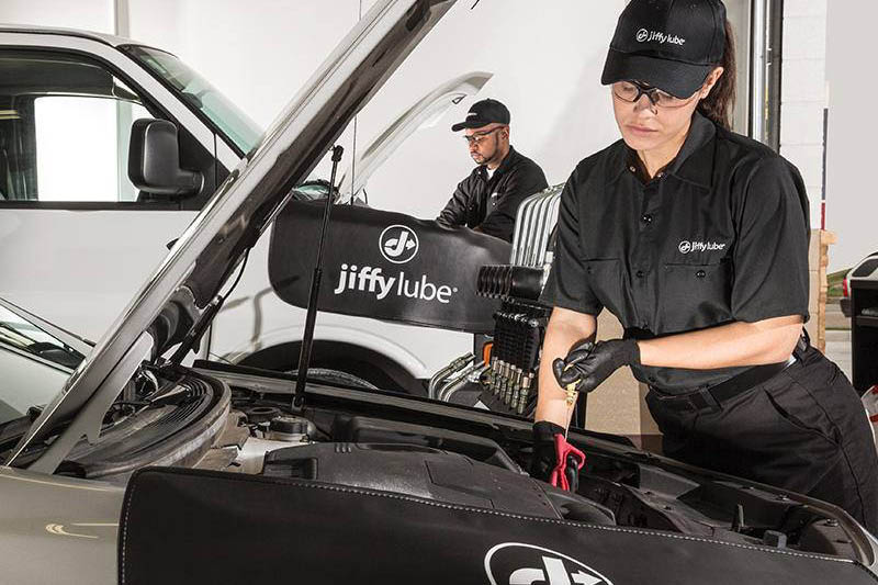 Jiffy Lube auto technician checking the oil on a car