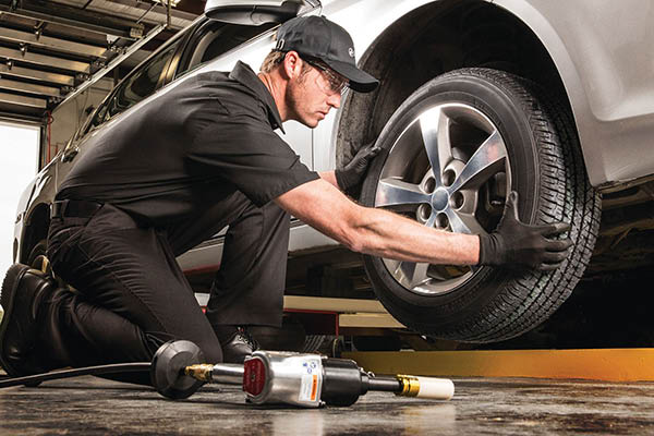 skilled auto tech performing a tire rotation service