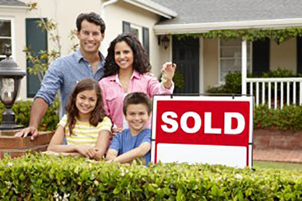 happy family standing outside newly sold house