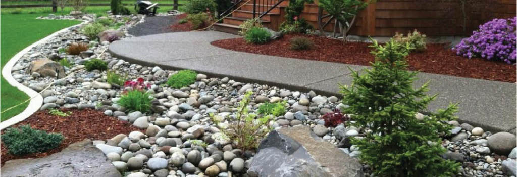 Landscaped area next to sidewalk featuring recycled stones, rocks and mulch