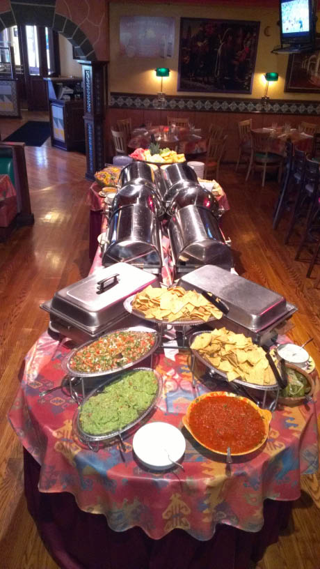 Mexican food buffet with chips and salsa and guacamole