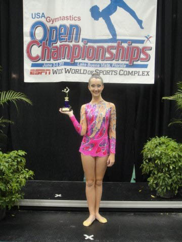 young female gymnast holding championship trophy; Miami Gymnastics instruction; summer camp