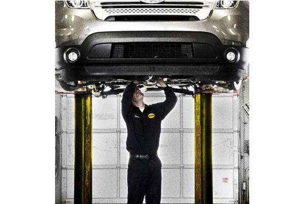 Midas technicians under car on lift in Arlington Texas; transmission service; mufflers