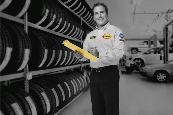 Rows of auto tires-Midas auto technician