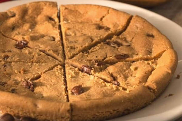 chocolate chip cookie cake on a white plate