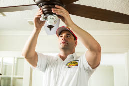 Mister Sparky electrician installing a ceiling fan in a home; electrical repairs in Florida